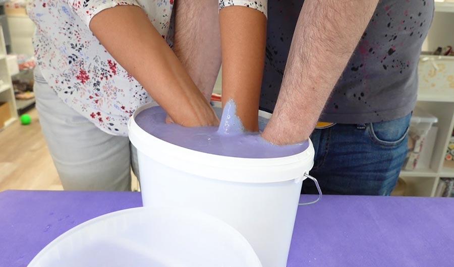 4 Hände stecken in Alginat um einen Handabdruck anzufertigen